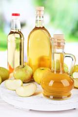 Apple cider vinegar in glass bottles and ripe fresh apples,
