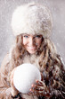 Beautiful young woman holding a snow ball