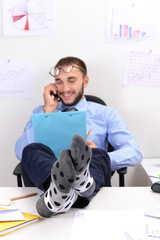 Confident businessman holding his legs in funny socks on desk