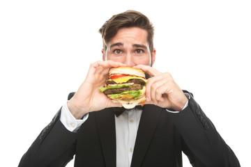 junger Geschäftsmann isst  großen Burger