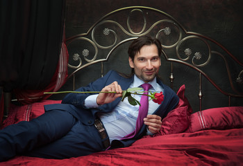 Smiling businessman lying on bed with flower