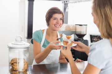 Pretty waitress serving muffin to customer