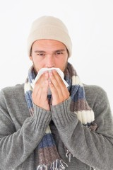 Young man in warm clothing sneezing