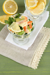 Tasty salad with shrimps and avocado, on wooden background