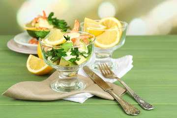 Tasty salads with shrimps and avocado in glass bowl and