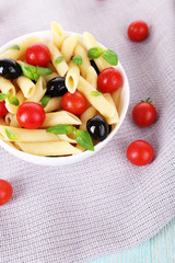 Pasta with tomatoes, olives and basil leaves in bowl on napkin
