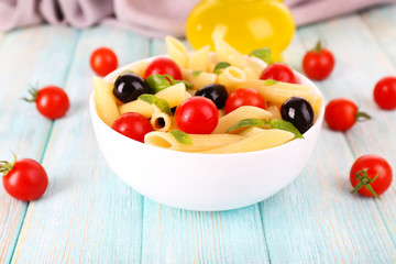 Pasta with tomatoes, olives and basil leaves in bowl and napkin