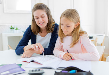 Woman helping out her little sister for homework