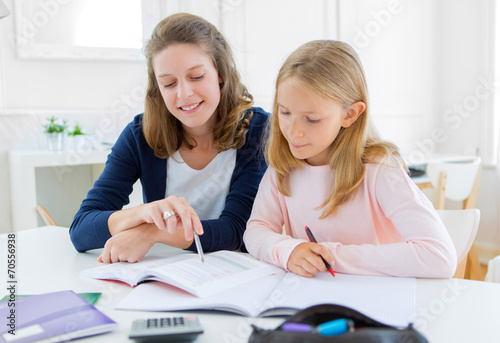 canvas print picture Woman helping out her little sister for homework