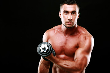Portrait of a sportsman lifting dumbbell over black background