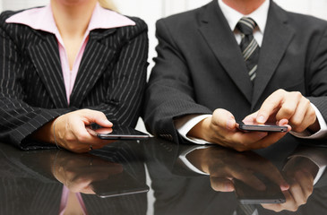 businessman and businesswoman using smart phone on meeting