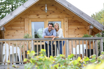 Couple standing in log cabin terrace