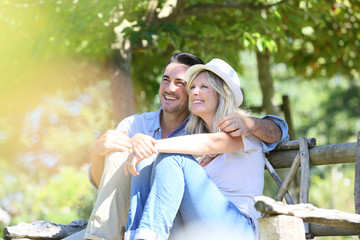 Couple relaxing on wooden bench in countryside