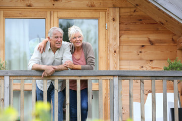 Senior couple standing oustide log cabin in countryside