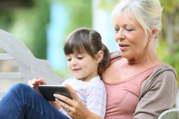 Senior woman with grandkid playing game on smartphone