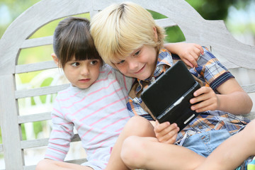 Kids sitting on outdoor bench and playing video games