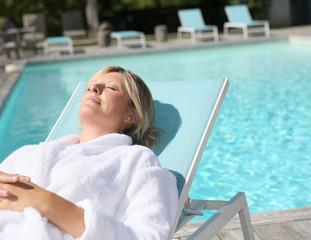 Closeup of woman relaxing in long chair by pool