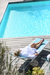 Senior woman relaxing in long chair by the pool