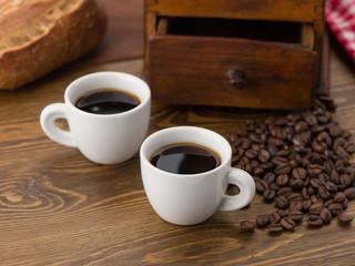 Kaffeetassen mit Kaffeemühle und Brötchen