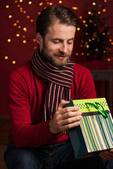 Christmas - smiling man opens gift bag on dark red with lights