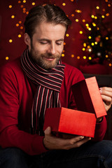 Christmas - smiling man opens present box on dark red