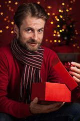 Christmas - smiling man opens present on dark red with lights