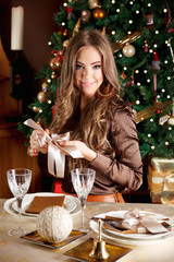 Beautiful young woman setting the Chrtismas table