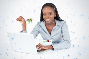 Businesswoman working with a notebook while eating a salad