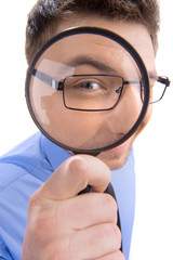 Curious man looking through magnifying glass.