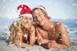 Composite image of couple lying on beach wearing christmas hats
