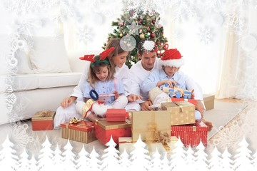Composite image of young family unpacking christmas presents