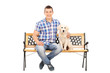 Casual man sitting on a bench with a puppy
