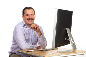 Satisfied man with glasses in hand sitting at computer
