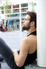 One man sitting outdoors on the floor in the city