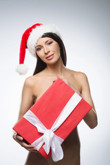 Beautiful naked model behind big Christmas gift.