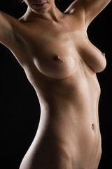closeup of nude young woman in front of black background.