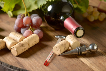 Stopper  with wine corks and bottle of wine on wooden