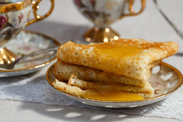 Russian pancakes with honey and cup of tea