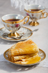 thin pancakes on a plate and cup of tea