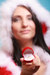 woman santa claus costume holds gift boxes with ring on blue