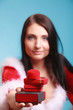 woman wearing santa claus costume holds gift boxes on blue