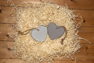 couple of blank grey wooden love hearts