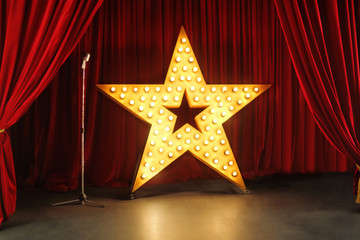 Scene with red curtains and big star with lights