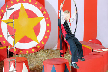 Little boy in a suit sitting on an air circus ring
