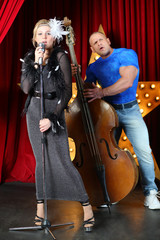 Beautiful singer and man with contrabass perform on stage
