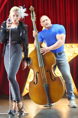 girl with microphone and man with big muscles with contrabass
