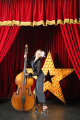 Beautiful woman in pop dress playing with contrabass on stage