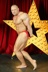 Bodybuilder shows his strength and muscles on stage