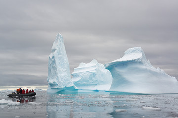 People in small inflatible zodiac rib boats passing towering sculpted icebergs on the calm water around small islands of the Antarctic Peninsula.