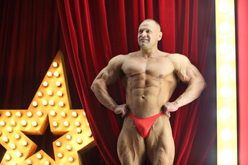 man with big muscles shows his physique on stage